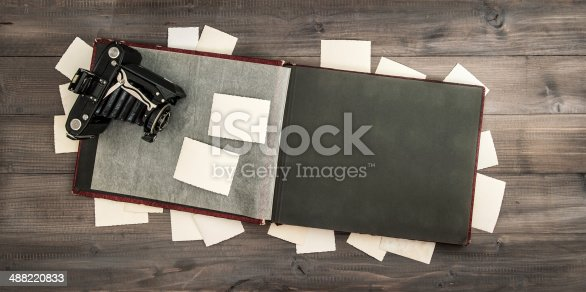 609706398 istock photo camera and album with old photos on wooden table 488220833