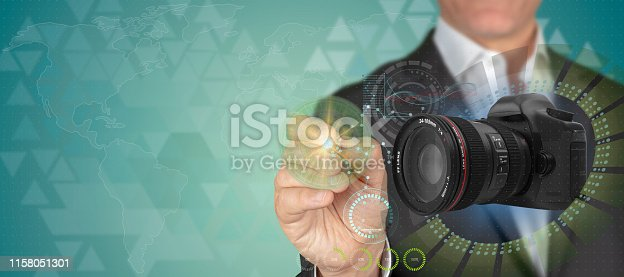 Camera and optics industry concept. Businessman pointing 3D No brand dslr camera object with pen in HUD patterned techno blue background with copy space