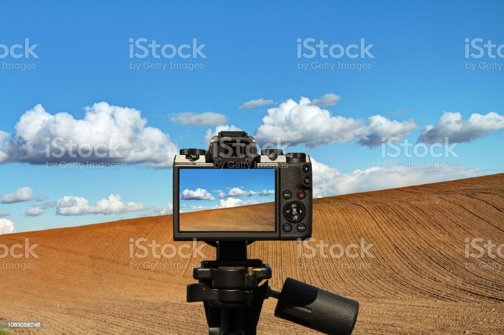 Camera and ideal for wallpaper picture field with clouds and blue sky