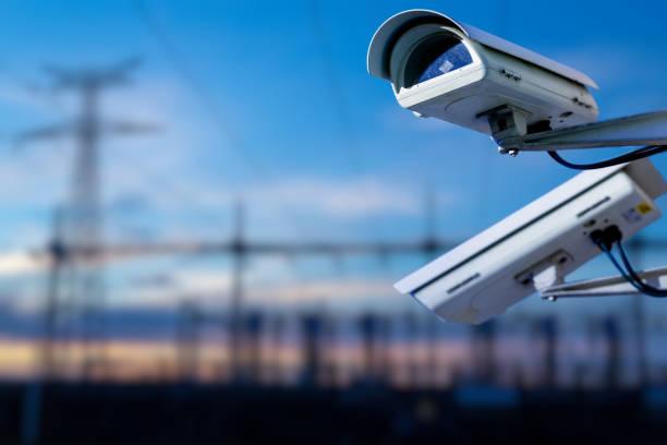 cctv camera concept met power station op de achtergrond - bewakingscamera stockfoto's en -beelden
