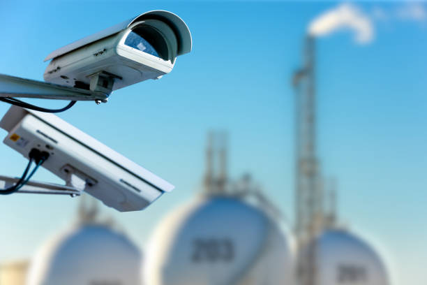 CCTV camera concept with refinery on background stock photo
