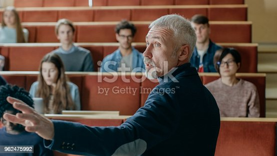 istock Camera Facing Class: College Professor Gives a Lecture to a Classroom Full of Multi Ethnic Students. Talented Speaker Captures Audience Attention. 962475992