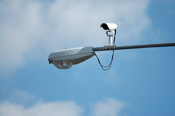 A camera installed on a streetlight watches traffic stock photo