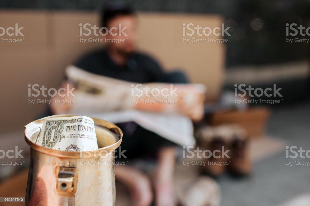 Câmera é focada em copo do metal com dólar nele. É Copa do mendigo. Mendigo é sentado em papelão e lendo jornal. Ele é relaxante - Foto de stock de Adulto royalty-free