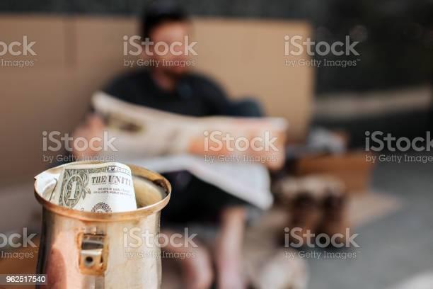Foto de Câmera É Focada Em Copo Do Metal Com Dólar Nele É Copa Do Mendigo Mendigo É Sentado Em Papelão E Lendo Jornal Ele É Relaxante e mais fotos de stock de Adulto