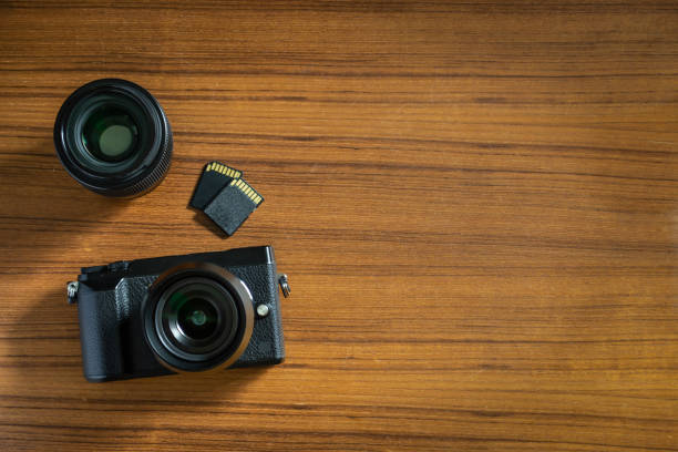camera, lens and memory card on table - memory card stock photos and pictures