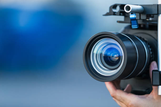 Camera lens attached to a camera and hand focusing close up detailed with smooth blue background and sunset reflections. Concept for videography cinematography vlogging video television movies making stock photo