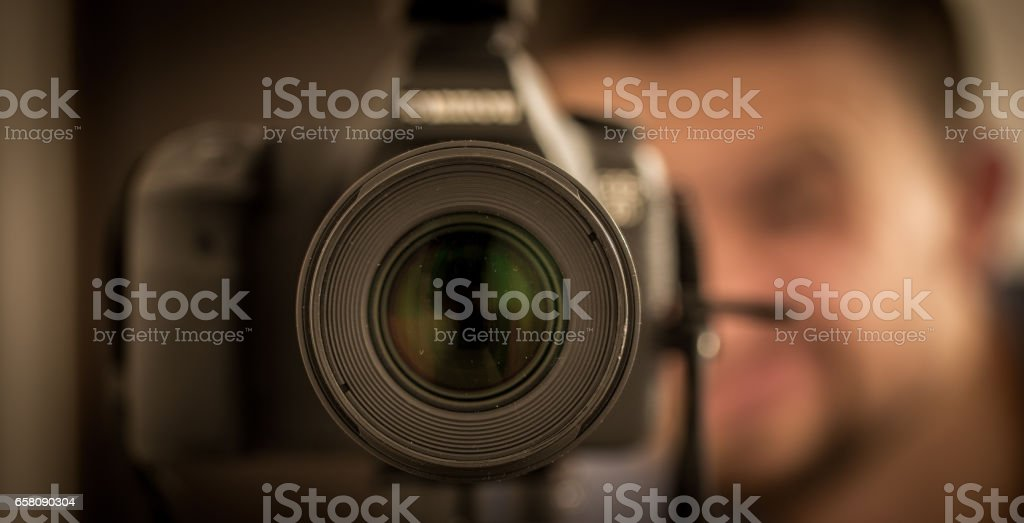 camera lens closeup with the man in the background royalty-free stock photo