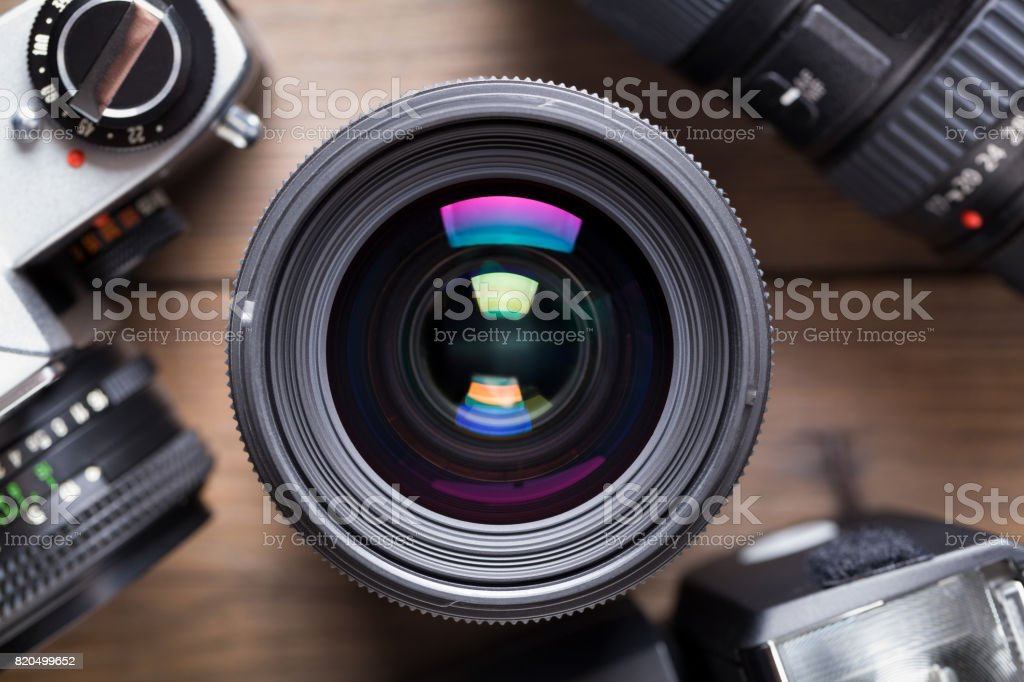 Camera lens on wooden table – zdjęcie