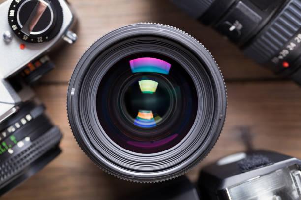 objectif de la caméra sur la table en bois - appareil photo photos et images de collection
