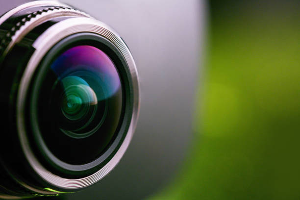 camera lens with green backlight. side view of the lens of camera on green background. greencamera lens close up. pure red - webcam stock pictures, royalty-free photos & images