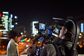 Behind the scenes shot of a camera operator shooting a scene with a businesswoman at night