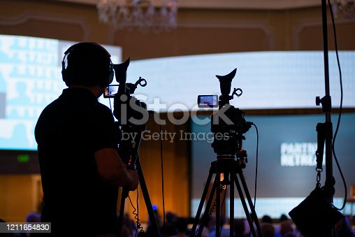 A camera man with two cameras frames his shot for the presentation about to take place on the stage. He is somewhat silhouetted and is wearing headphones.