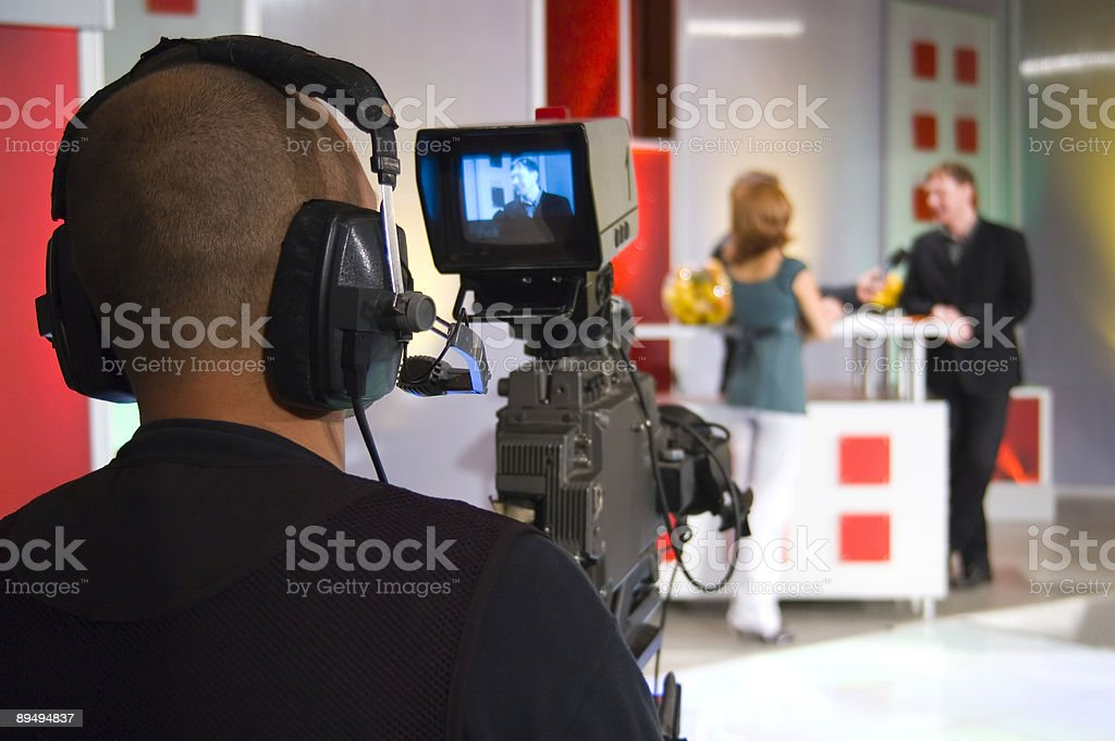 Camera man filming in TV studio stock photo
