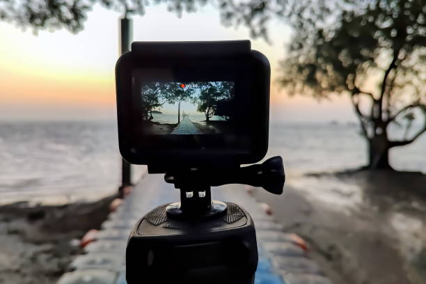 Camera mounted on a tripod photograph the pier and sunrise. Close up, view on screen, stock photo