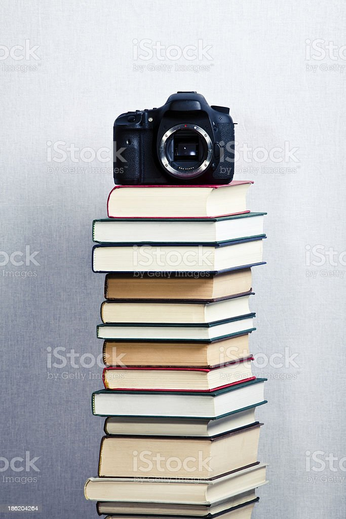 Camera on a high stack of books stock photo