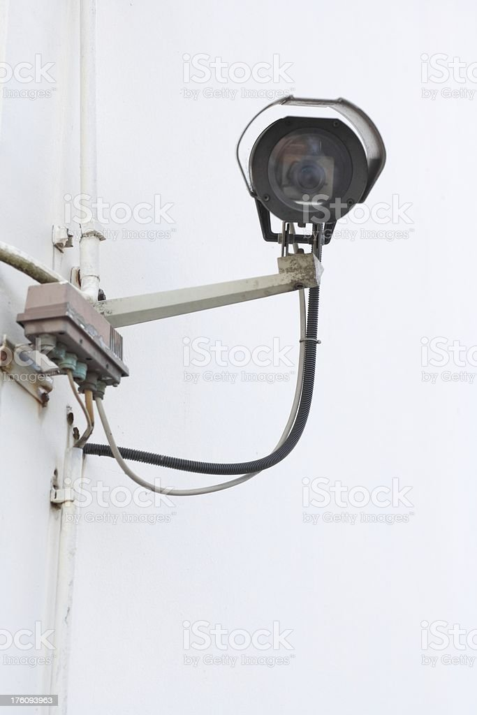 CCTV camera on a wall bracket, off a building. royalty-free stock photo