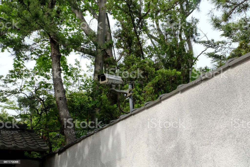 CCTV Camera on grey concrete wall. CCTV security camera for home protection, privacy, security against crime & surveillance. Closed circuit camera on gray wall background. stock photo
