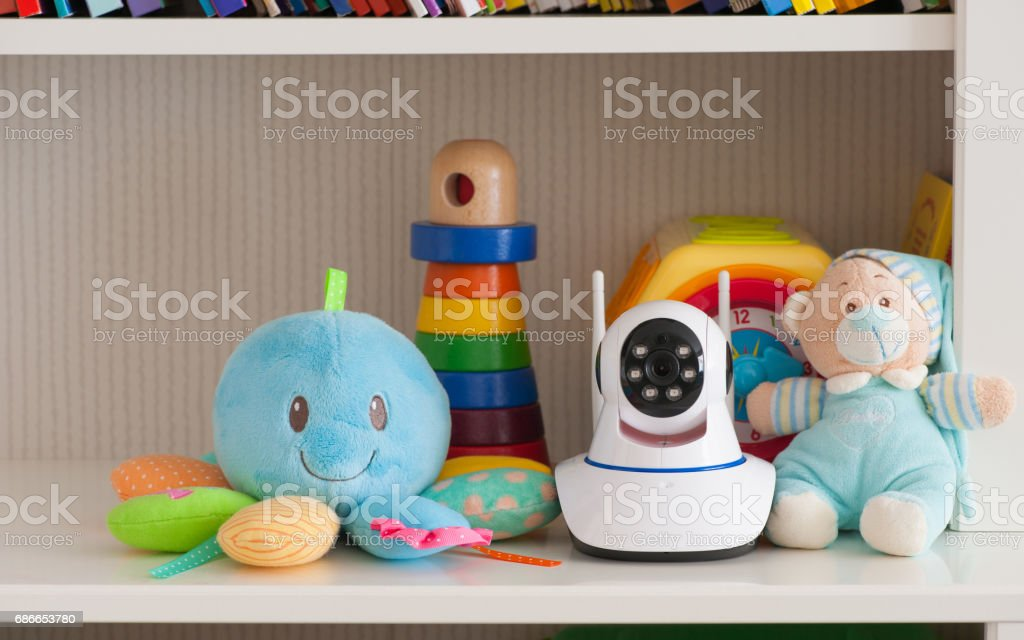 IP camera on the shelf with toys, serving as a baby monitor stock photo