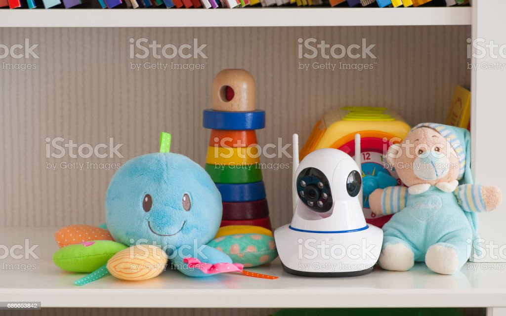 IP camera on the shelf with toys, serving as a baby monitor royalty-free stock photo