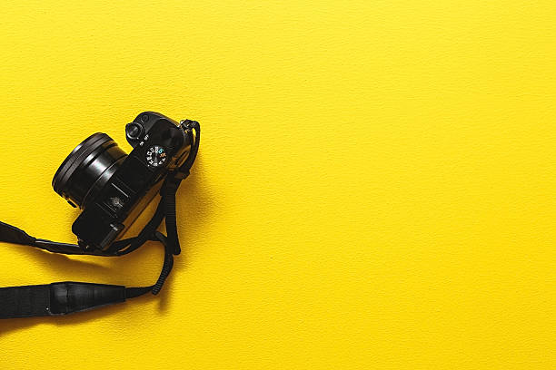 camera on yellow background - camera photographic equipment stock photos and pictures