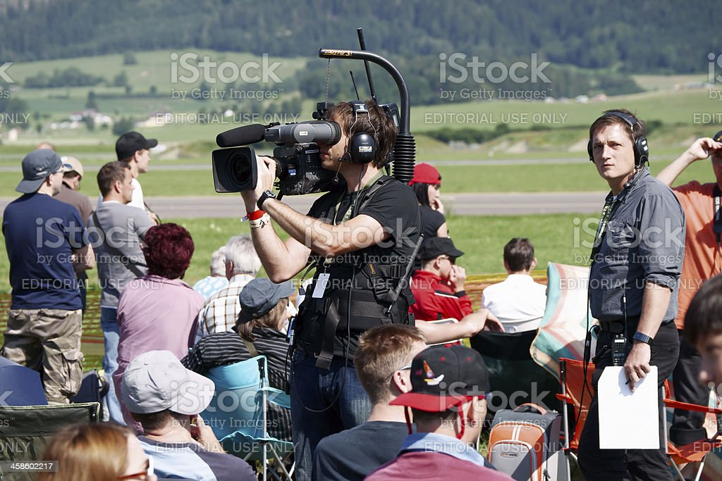 Camera operator with professional video-camera in the crowd royalty-free stock photo
