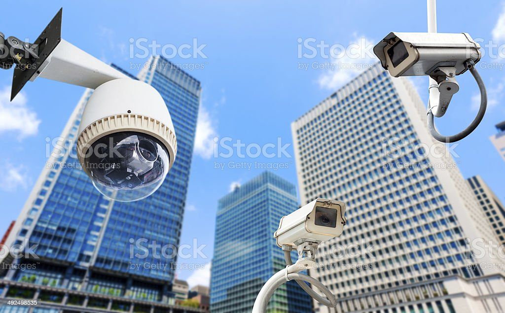 CCTV Camera or surveillance oeprating with building in backgroun stock photo