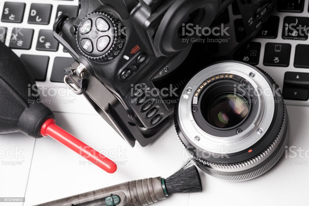 Camera, lens and cleaner tools on laptop