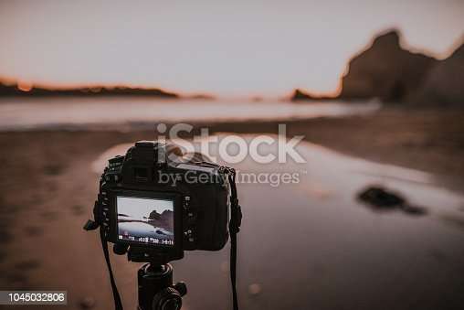 A DSLR taking a picture at sunset, mounted on a tripod