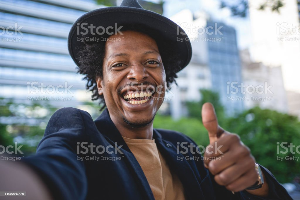 Camera point of view of an African American man holding thumbs up African American man exploring Buenos Aires and taking selfies 30-34 Years Stock Photo