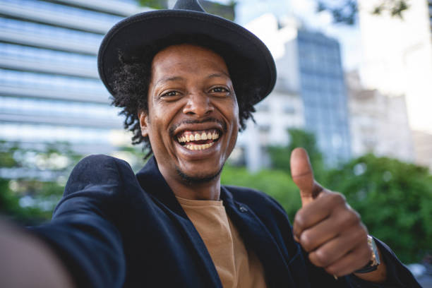 Camera point of view of an African American man holding thumbs up stock photo