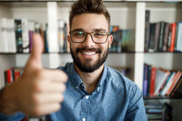 Camera point of view of young man holding thumbs up at home office stock photo