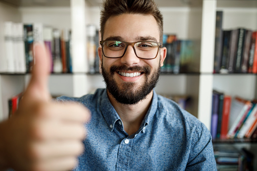 Camera point of view of young man holding thumbs up at home office
