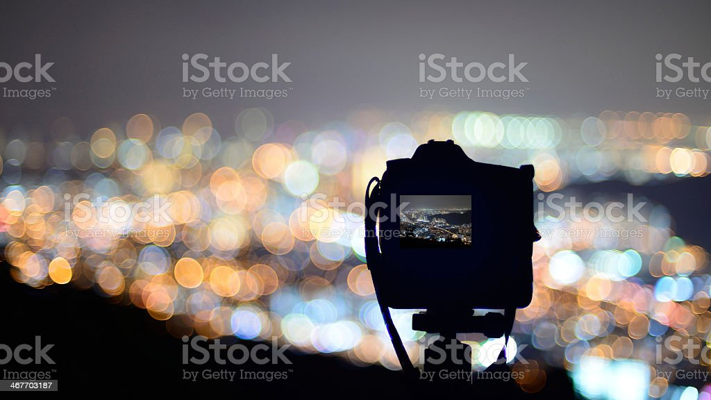 Camera pointing at a view of a city at night stock photo
