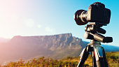 Digital SLR camera set up on a tripod to shoot a timelapse video sequence at dawn. The setting is Cape Town, South Africa, and the mountain is Table Mountain.