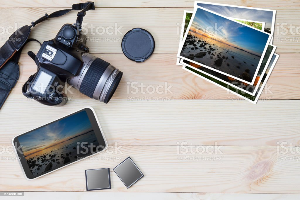 DSLR camera, smartphone, photos and memory card on wooden background stock photo