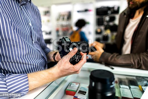 Camera store seller showing various camera lenses on a mirrorless camera to his customer in a camera accessories store.
