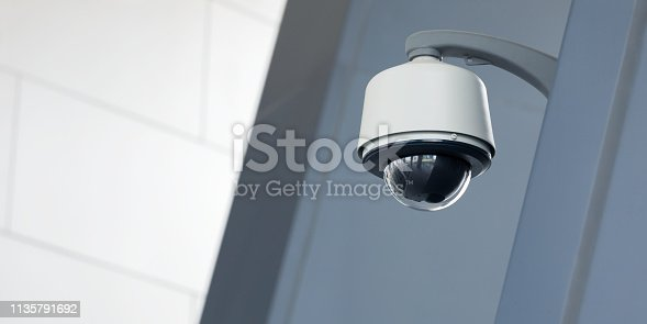 A modern dome camera on an office building facade.