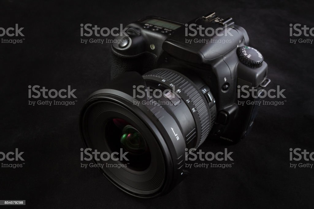 Camera with wide angle lens isolated on black background, elevated viewpoint stock photo