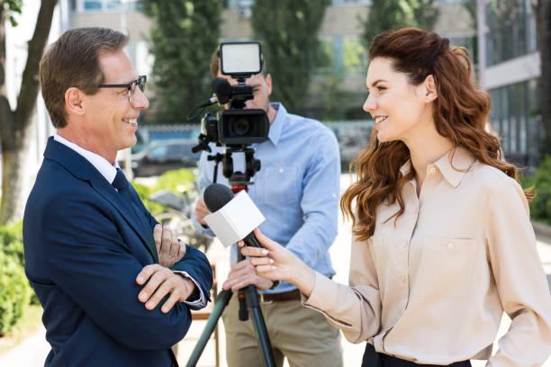 camarógrafo y mujer periodista con el empresario profesional entrevistas micrófono - periodista fotografías e imágenes de stock