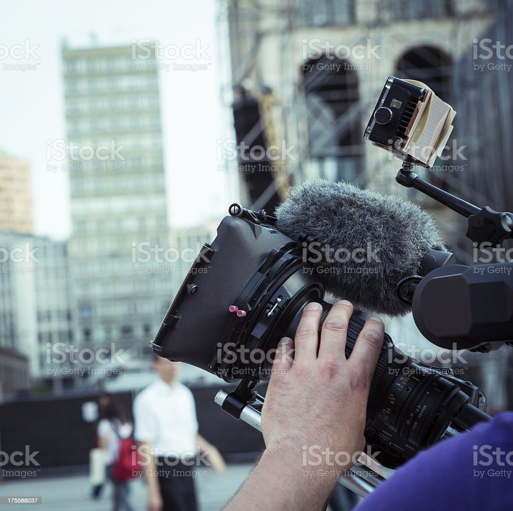 Cameraman at work holding his camera with his left hand stock photo