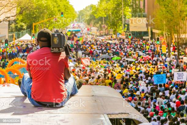 Cameraman Filming Floats And Fancy Dress Costumes At The Gauteng Carnival In Pretoria From The Top Of A Bus Stock Photo - Download Image Now