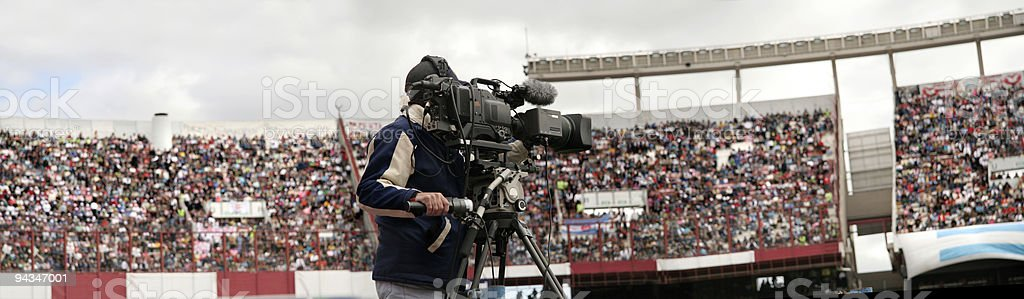 Cameraman filming in full soccer stadium stock photo
