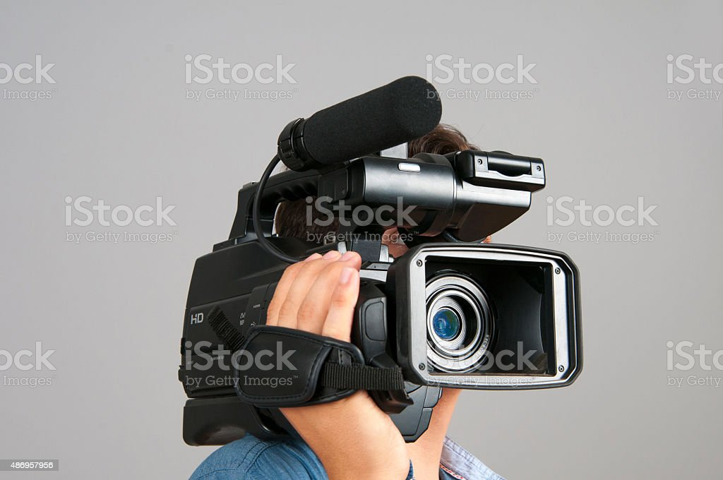 Cameraman holding a camera on his shoulder isolated on gray stock photo