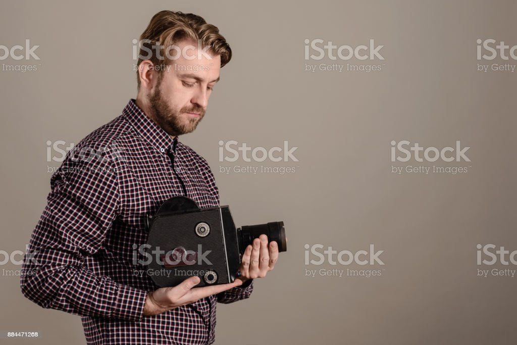 Cameraman in a checkered shirt gently holds an old movie camera in his hands stock photo