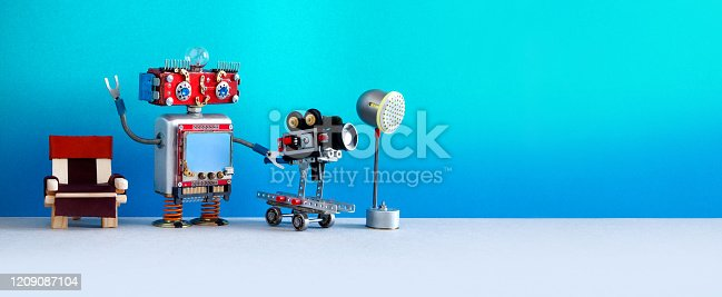 910163152 istock photo Cameraman shoots motion picture television episode or movie. Funny robotic filmmaker operator with retro camera, director chair and spotlight behind the scenes. copy space 1209087104