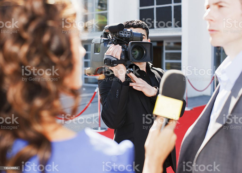 Cameraman taping celebrity on red carpet stock photo