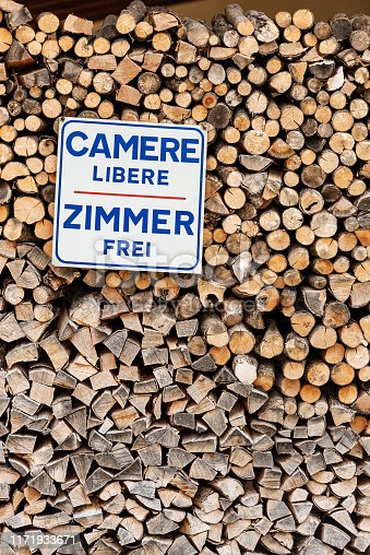 Rooms available in Italian and German language (Camere libere and Zimmer frei). Advertising sign hanging on a stack of firewood