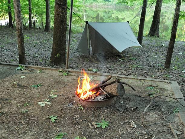 camfire und modernen camping hängematte unter plane - planenzelt stock-fotos und bilder