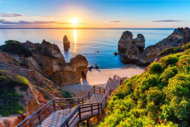 camilo beach (praia do camilo) in de algarve, portugal met turquoise zee op de achtergrond. houten voetgangersbrug naar beach praia do camilo, portugal. prachtig uitzicht op camilo strand in lagos, algarve, portugal. - portugal stockfoto's en -beelden